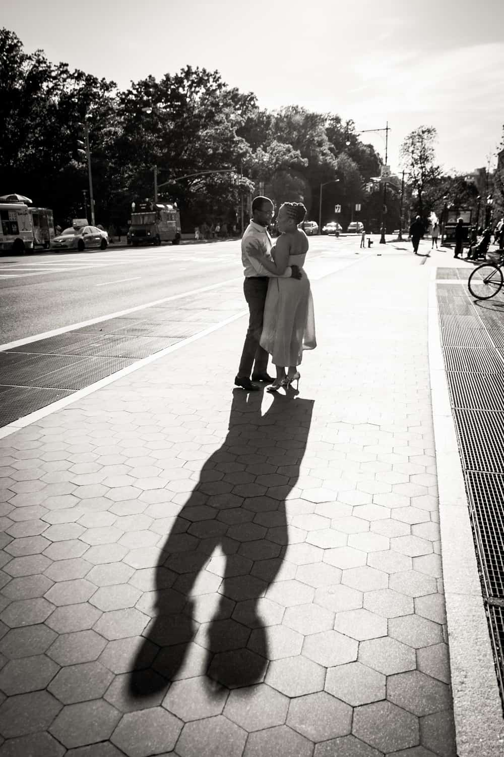 Black and white photo of couple kissing on sidewalk and resulting shadow