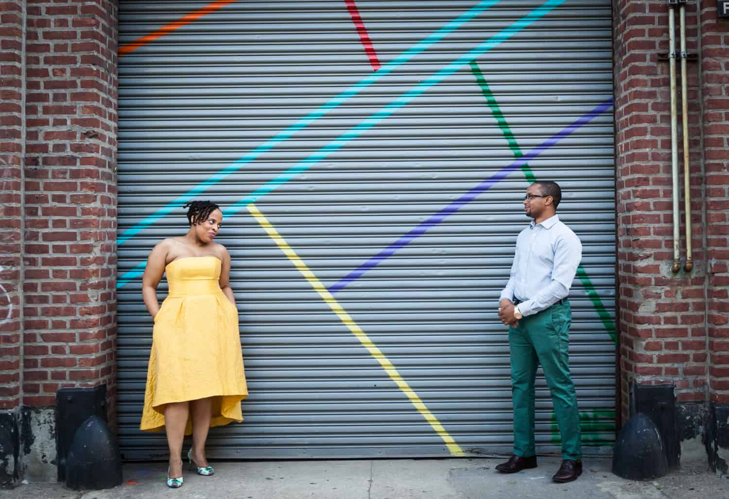 Couple standing in front of metal gate of Five Myles gallery in Brooklyn