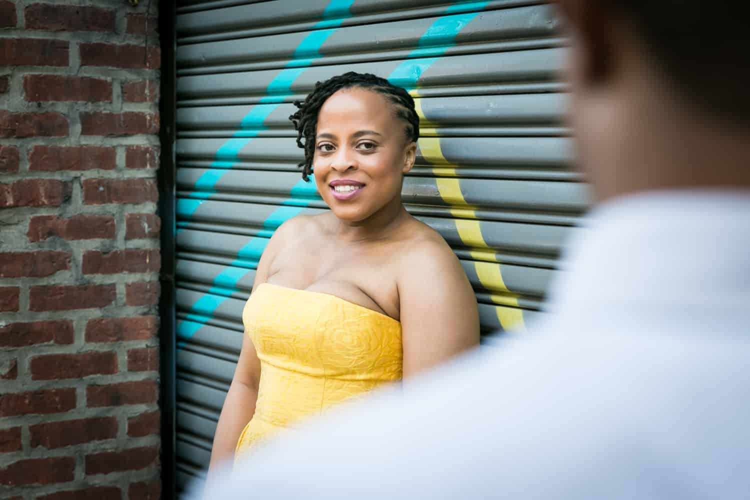 African American woman wearing strapless yellow dress looking at man