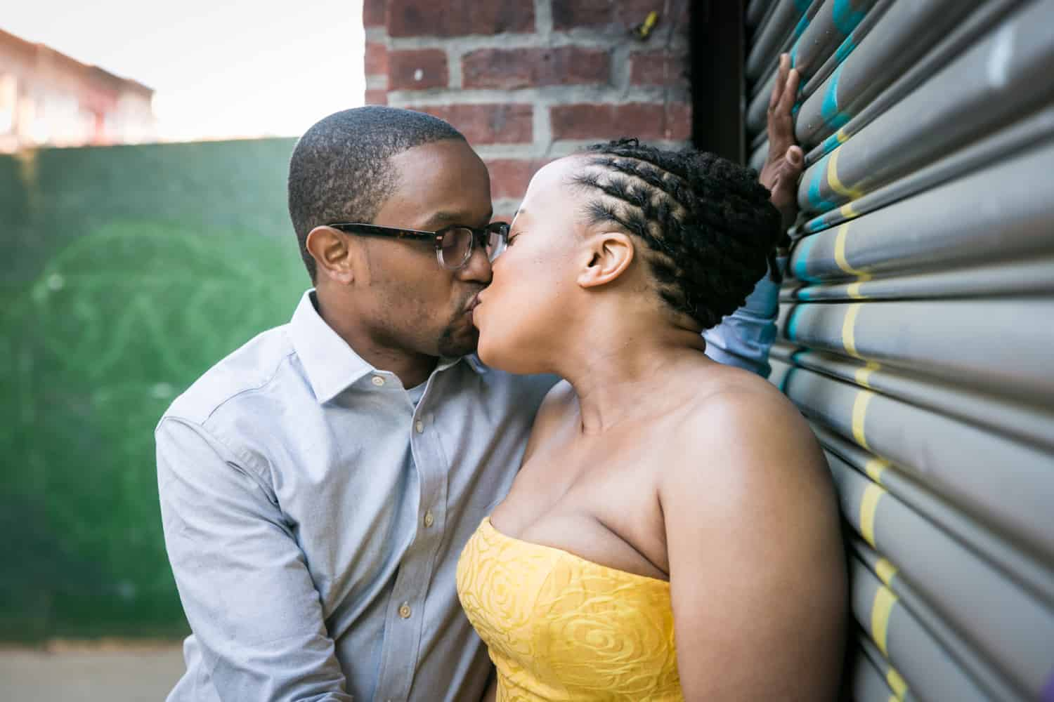 Couple kissing against metal gate in Brooklyn