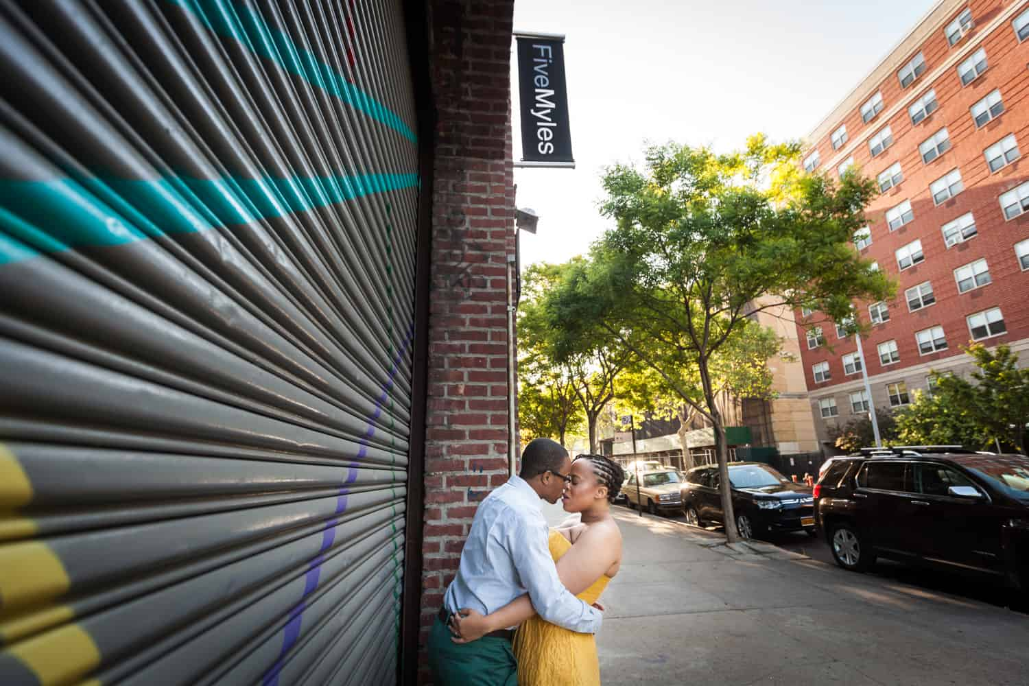 Couple kissing in front of metal gate in Brooklyn