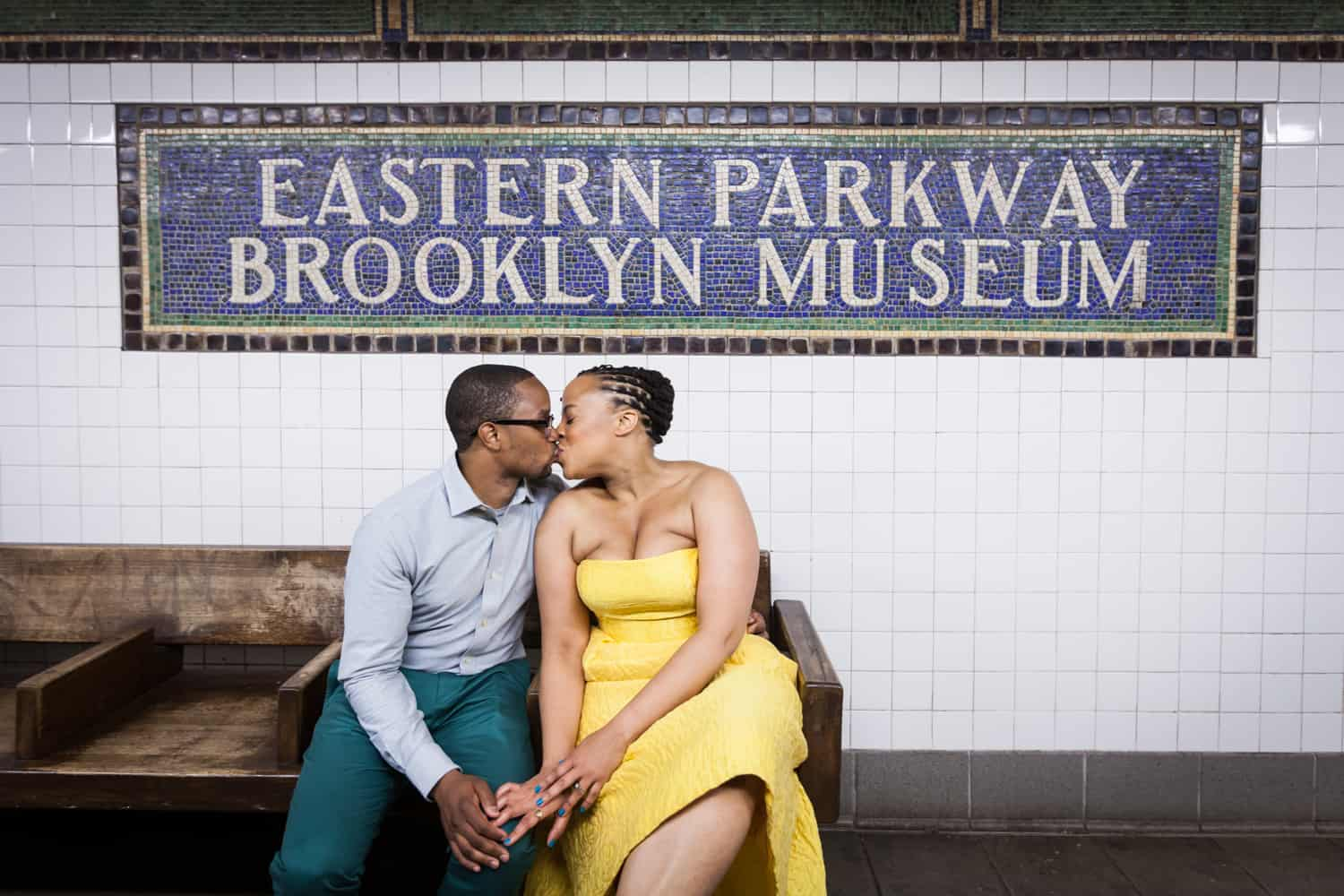 Couple sitting and kissing under Eastern Parkway Brooklyn Museum subway platform