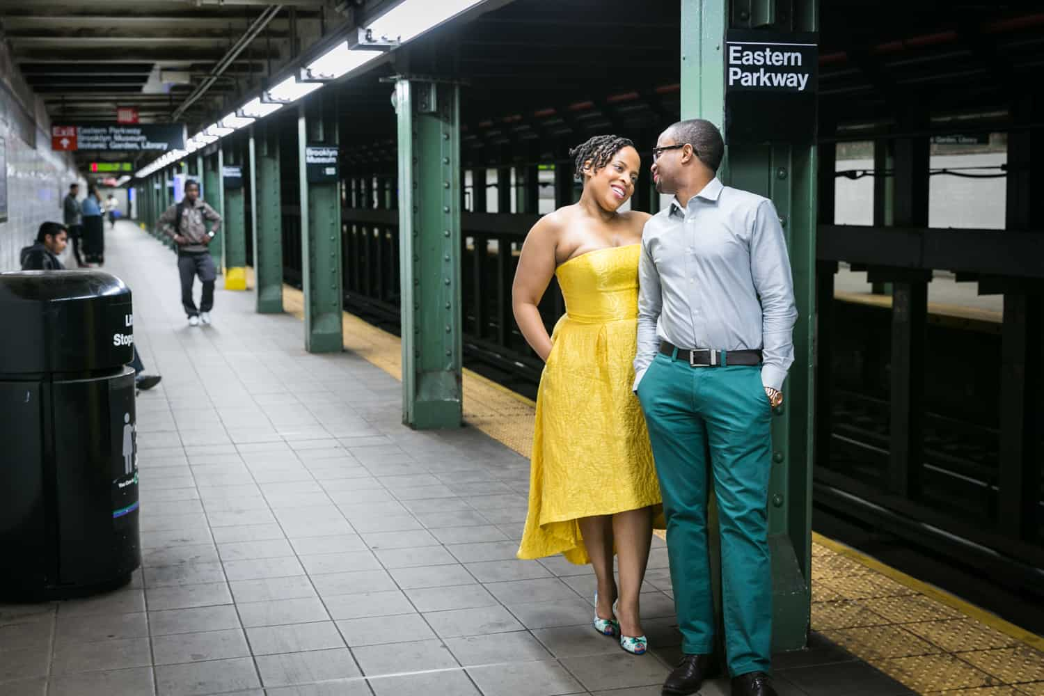 African American couple standing against column on subway platform