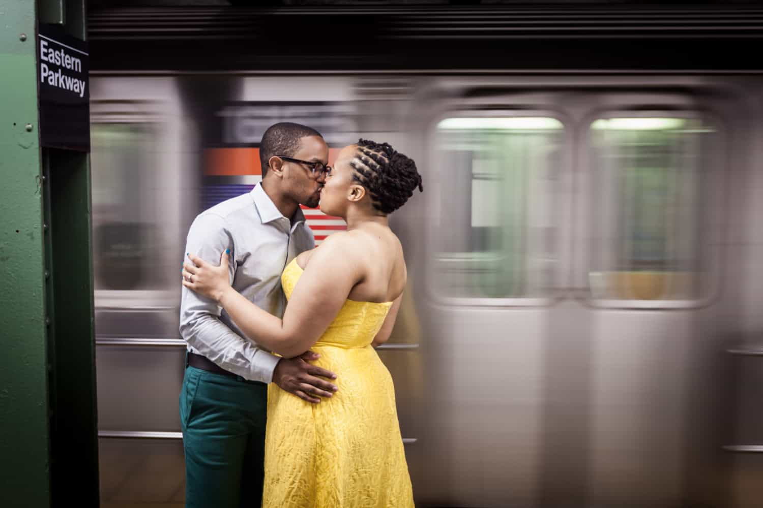 African American couple kissing in front of speeding subway train