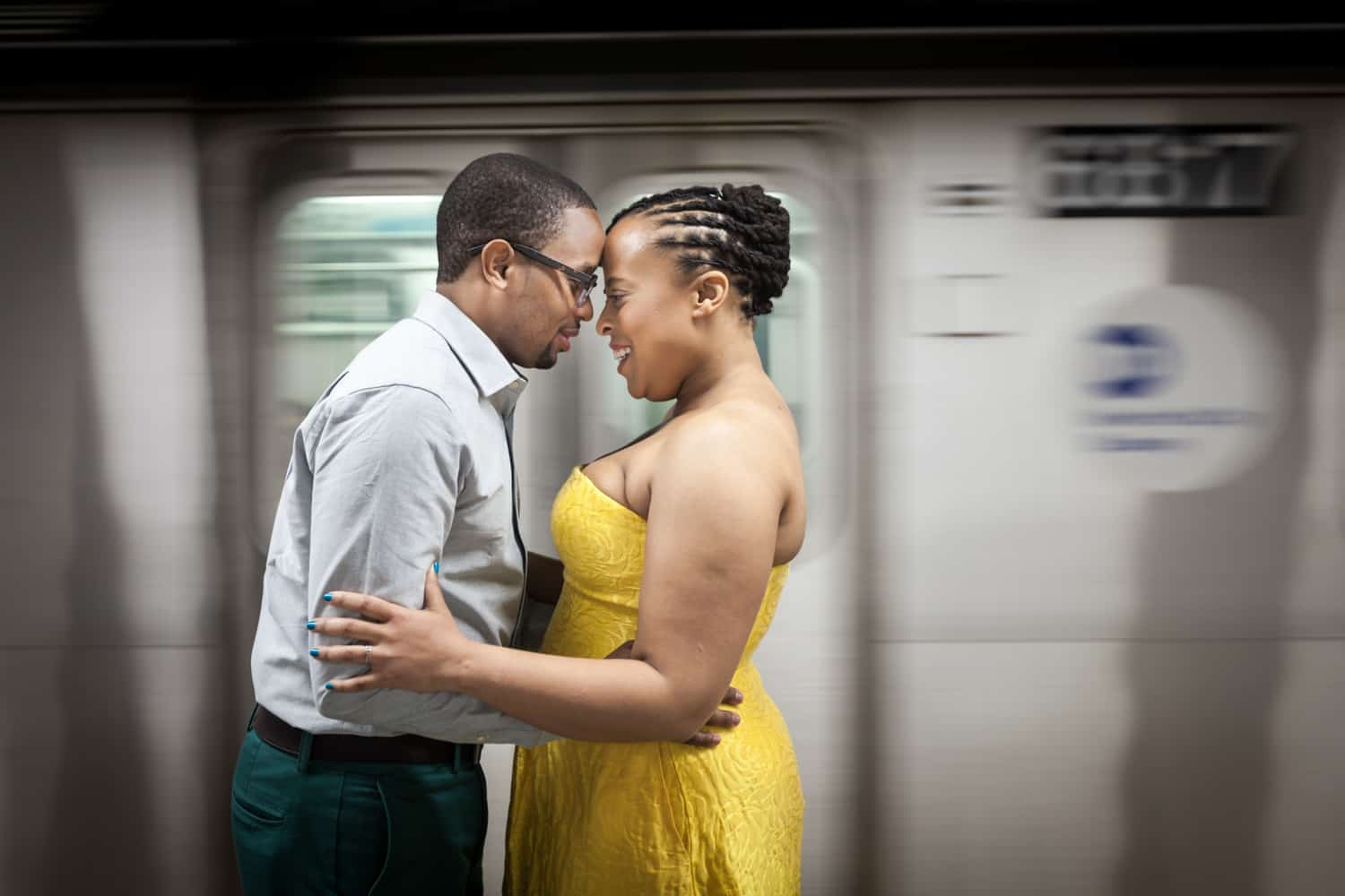 African American couple touching foreheads in front of speeding subway train