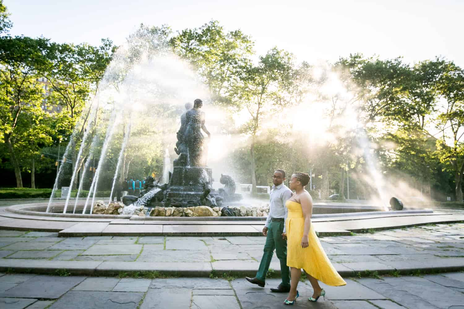 African American couple walking past fountain at Grand Army Plaza