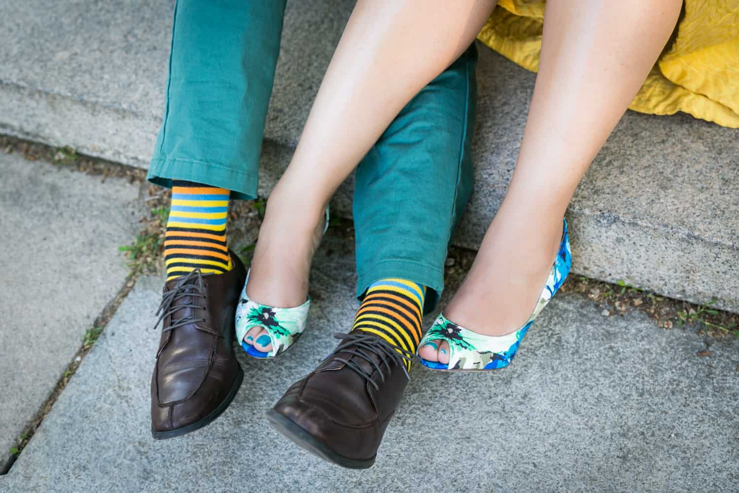 Close up on woman wearing colorful floral heels and man wearing colorful socks and black shoes