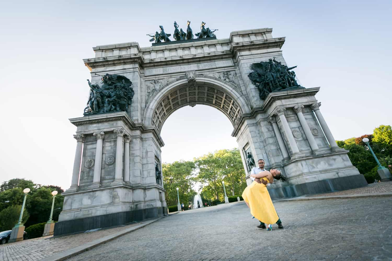 Wide shot of African American couple dancing in front of Grand Army Plaza arch