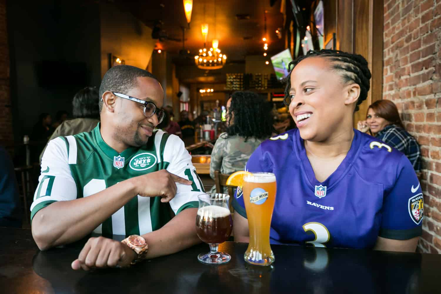 African American couple sitting at bar and wearing football jerseys