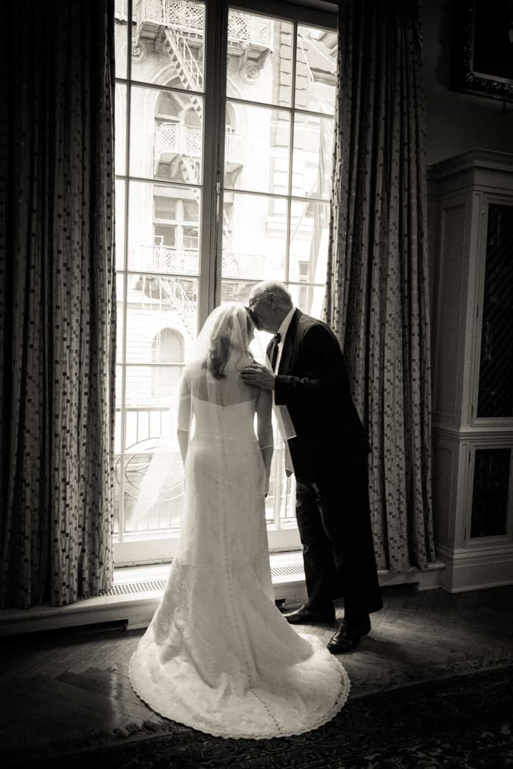 Black and white photo of father kissing bride in front of window before a Harvard Club wedding