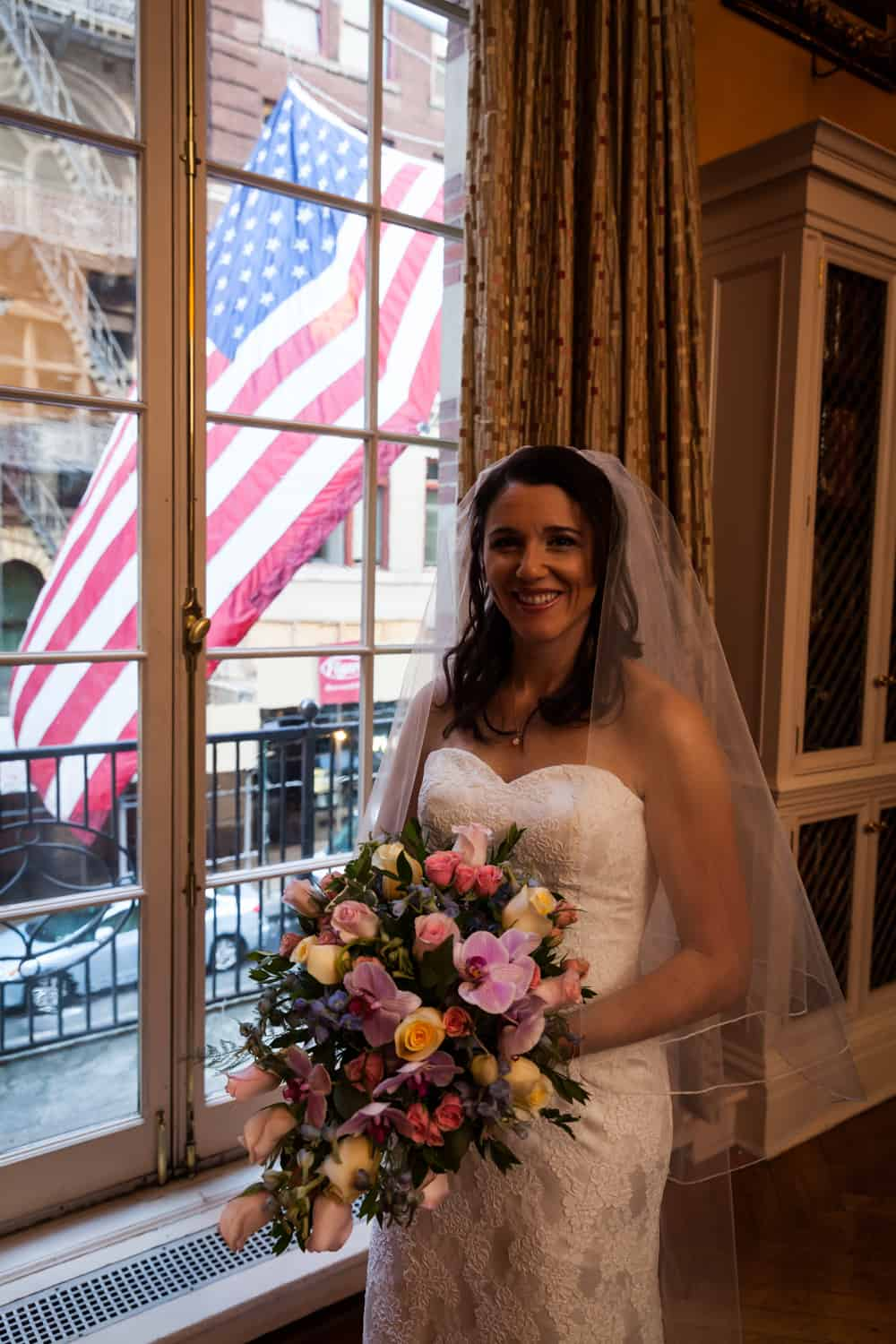 Bride holding bouquet by window for an article on the mysteries of photo editing