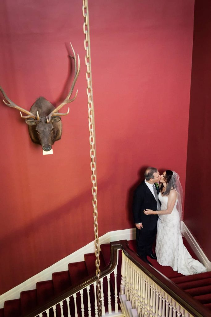 Bride and groom in corner of staircase with moose head on wall before a Harvard Club wedding