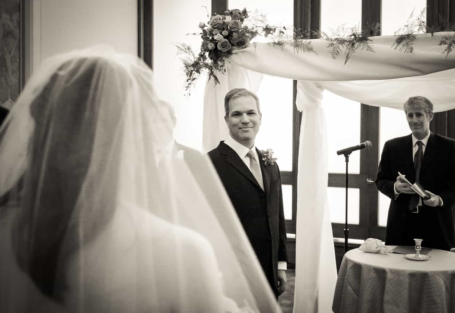 Black and white photo of groom seeing bride during Harvard Club wedding ceremony