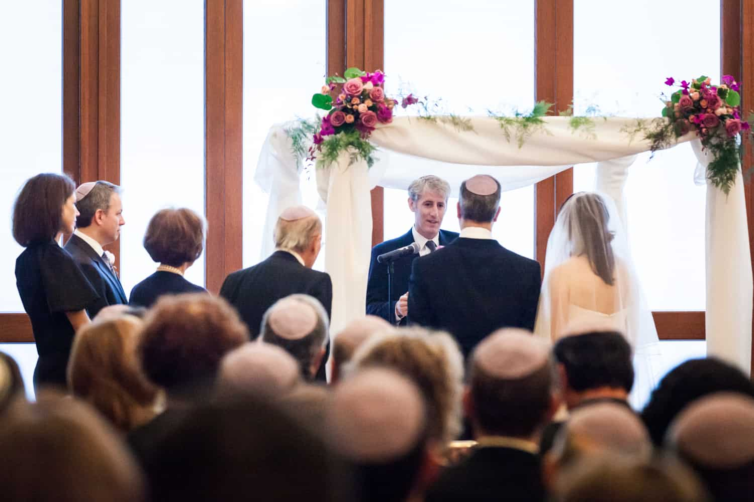 Bride and groom under chuppah during Harvard Club wedding ceremony