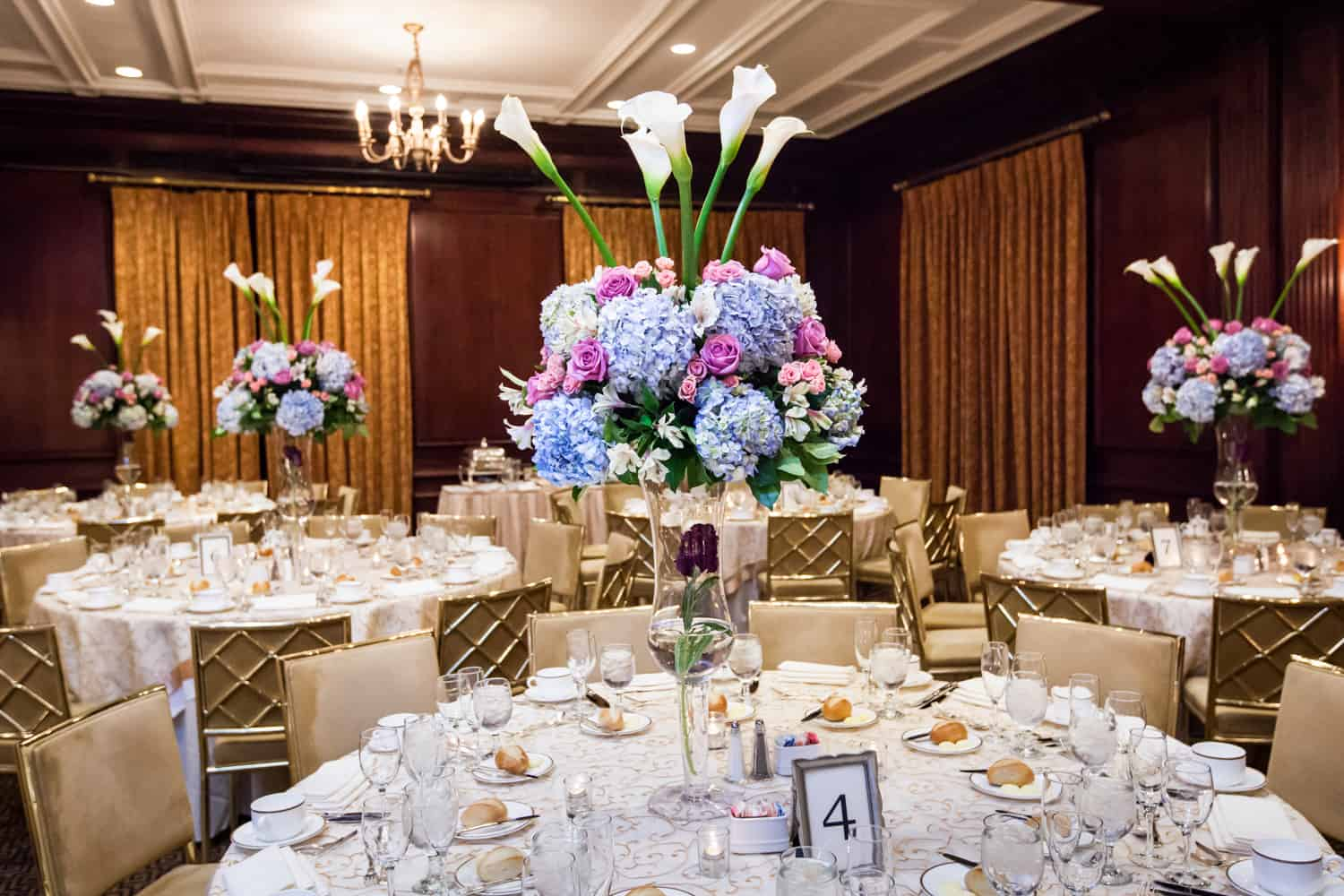 Table settings with large floral centerpieces at Harvard Club wedding reception