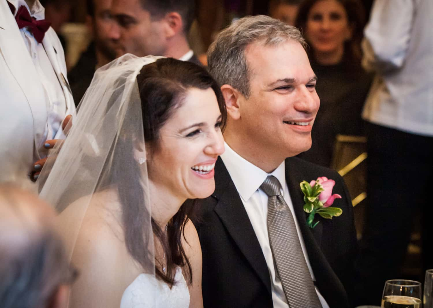 Bride and groom smiling at reception for an article on the mysteries of photo editing