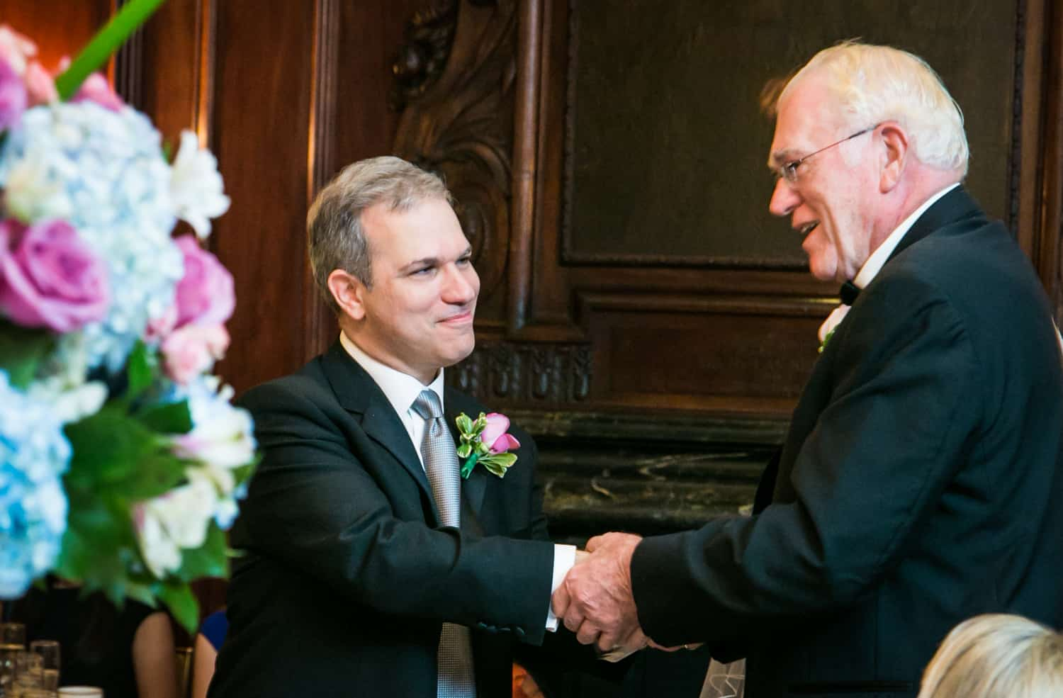 Groom shaking hands with older gentleman at Harvard Club wedding
