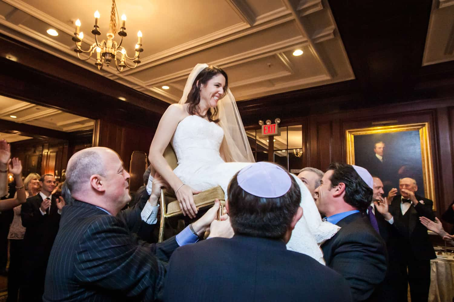 Bride lifted up on chair during hora dance at Harvard Club wedding