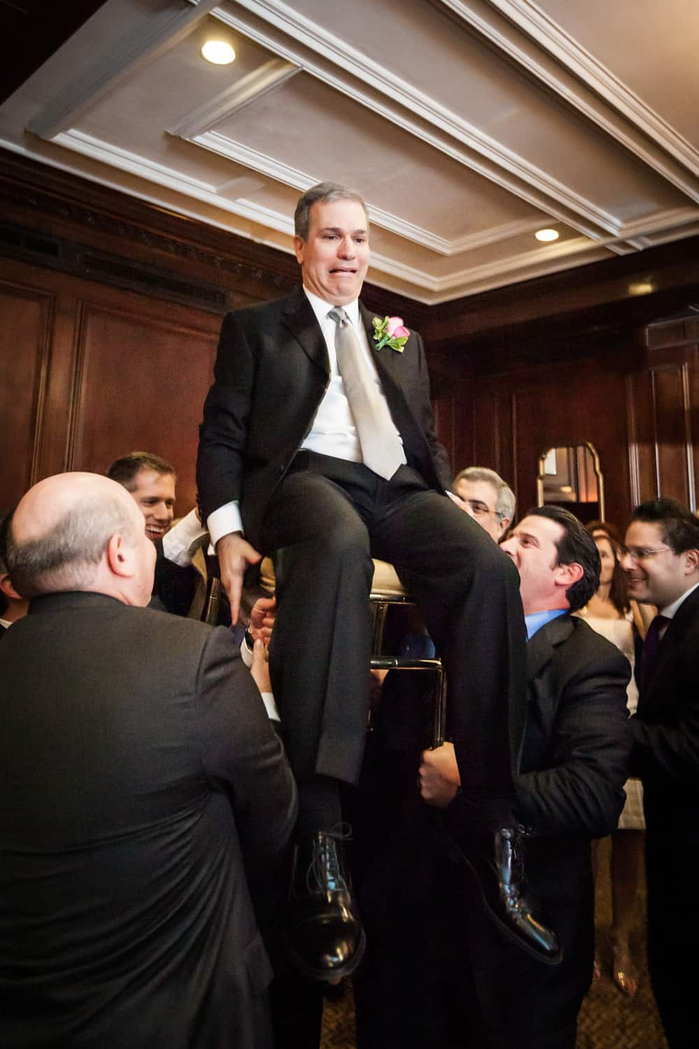 Groom lifted up on chair during hora dance at Harvard Club wedding