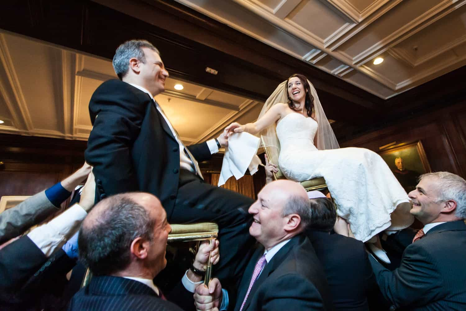 Bride and groom up on chairs during hora dance at Harvard Club wedding