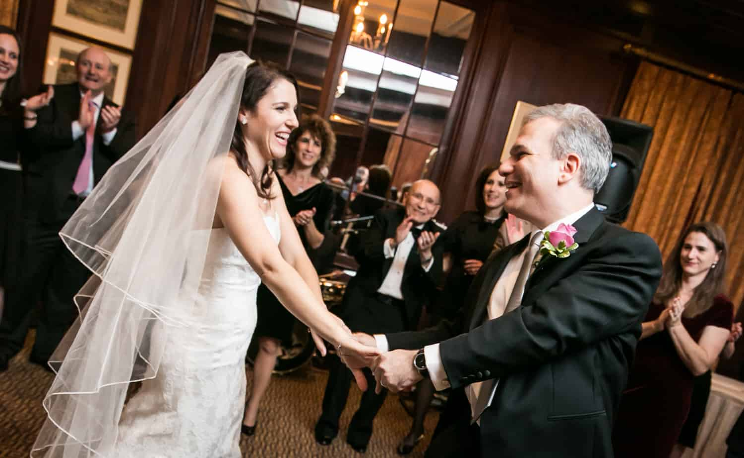 Bride and groom holding hands and dancing the hora at Harvard Club wedding