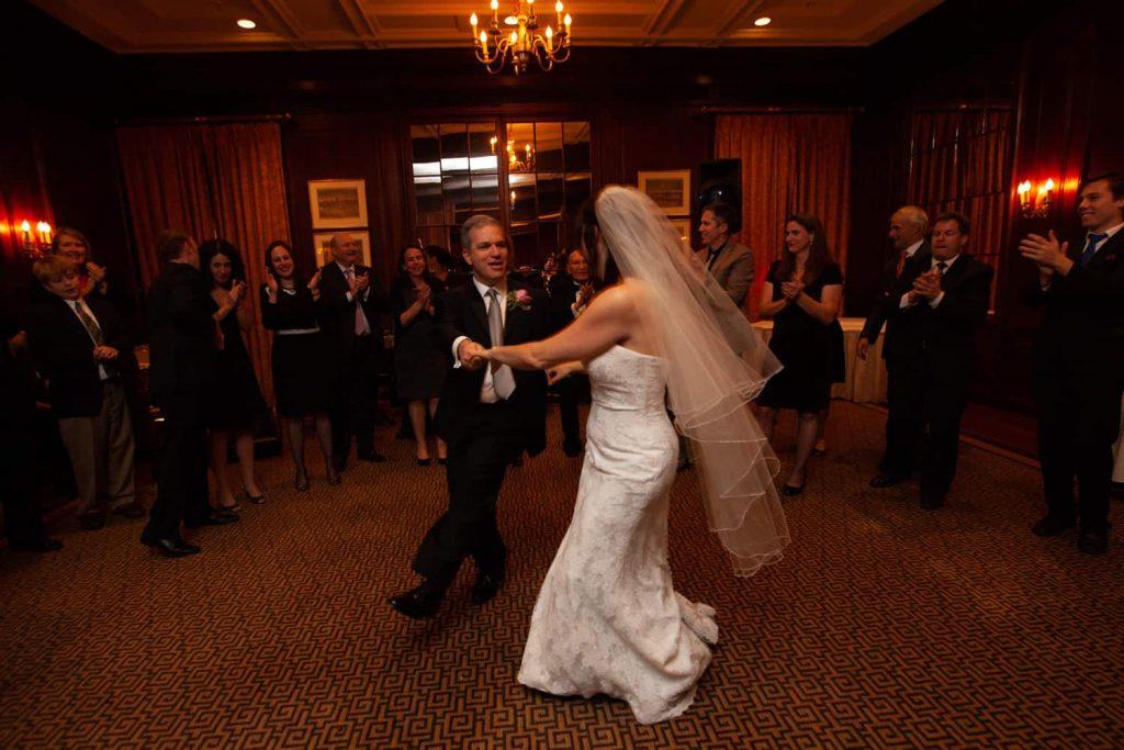 Bride and groom dancing in front of guests for article on the mysteries of photo editing