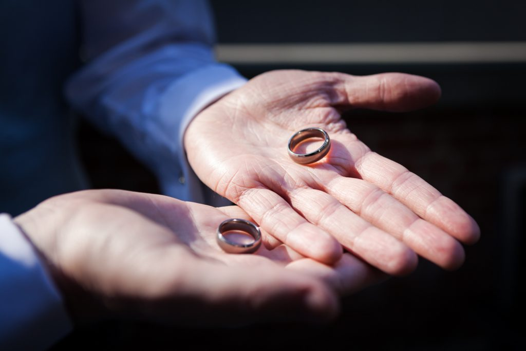 Close up on hands of two men holding wedding rings