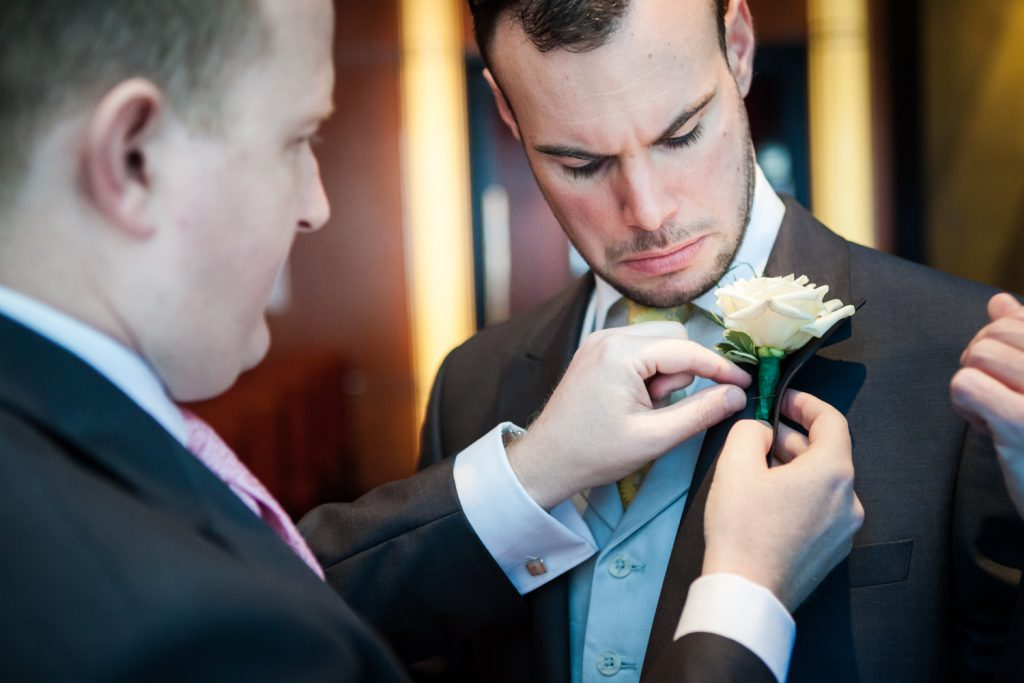 Man putting boutonniere on other man