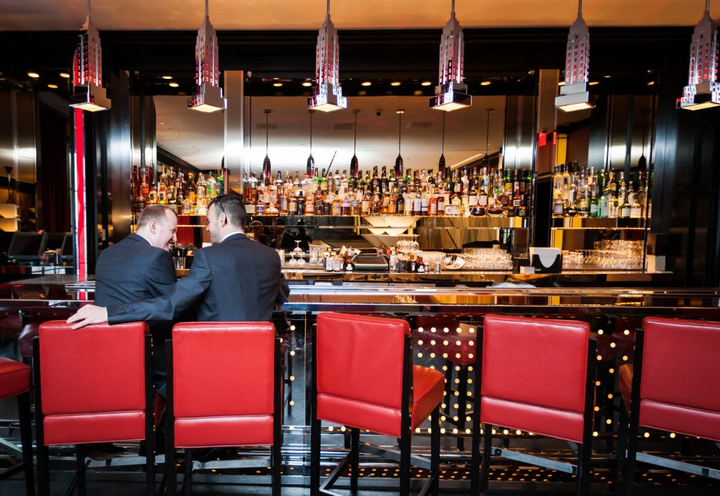 Two grooms sitting in red seats at a Chatwal Hotel bar