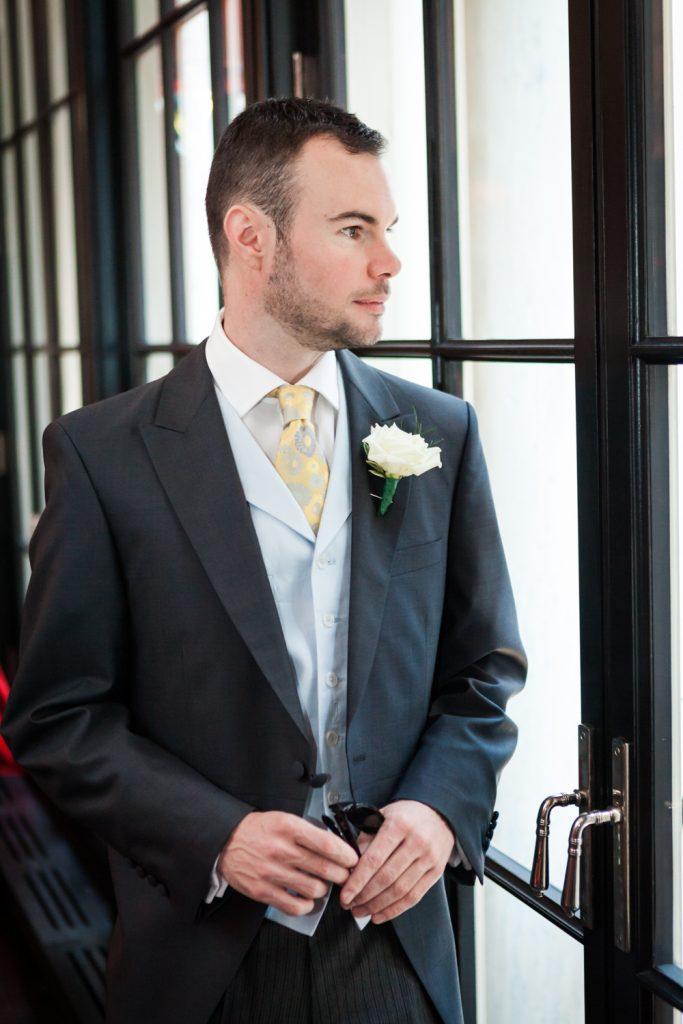 Groom standing in front of window