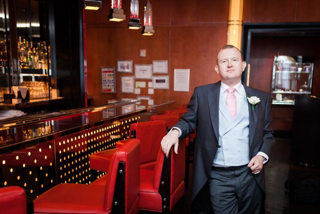 Groom holding on to red chair in Chatwal Hotel bar