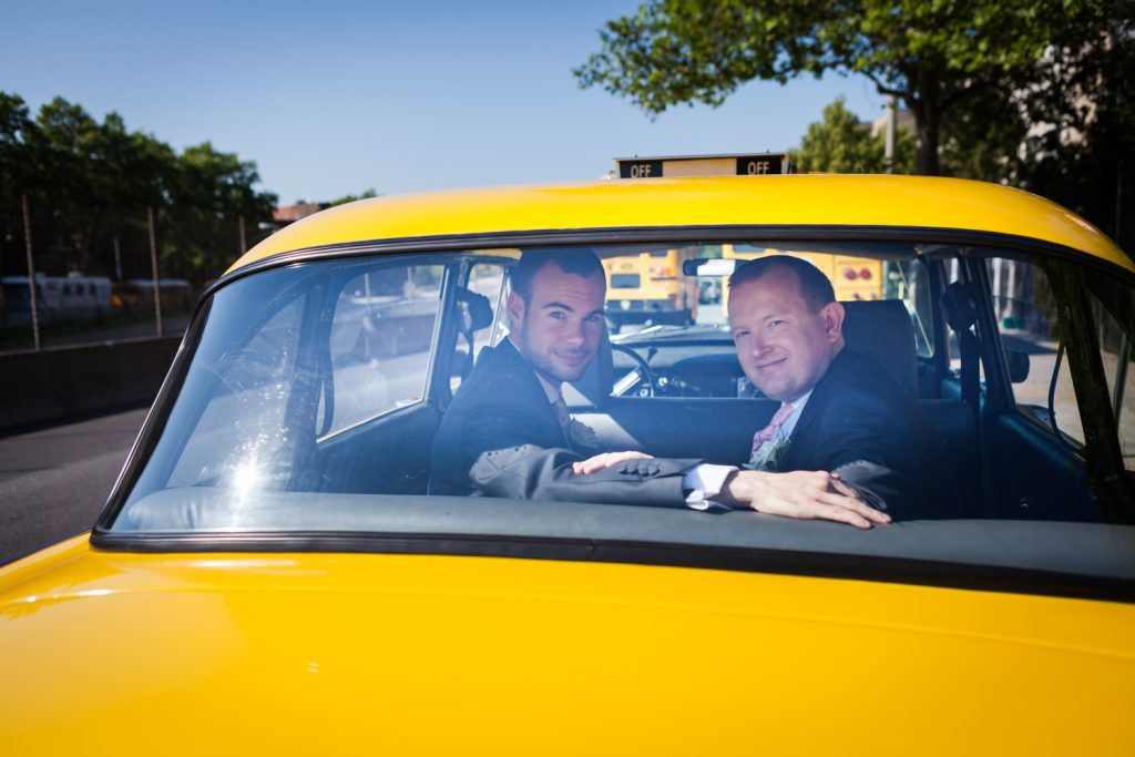 Two men looking out back window of NYC taxi cab