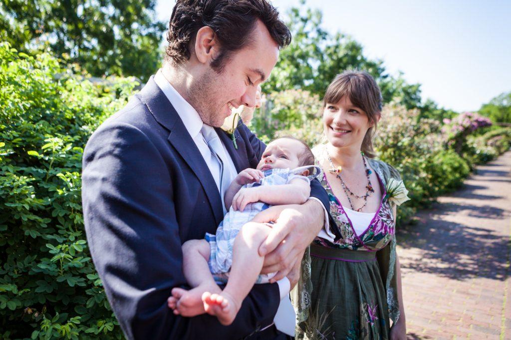 Woman watching man holding baby at an Brooklyn Botanic Garden wedding
