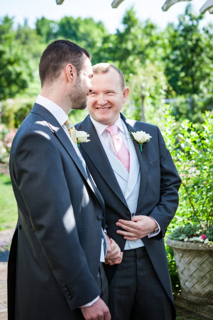 Two grooms looking at each other at an Brooklyn Botanic Garden wedding