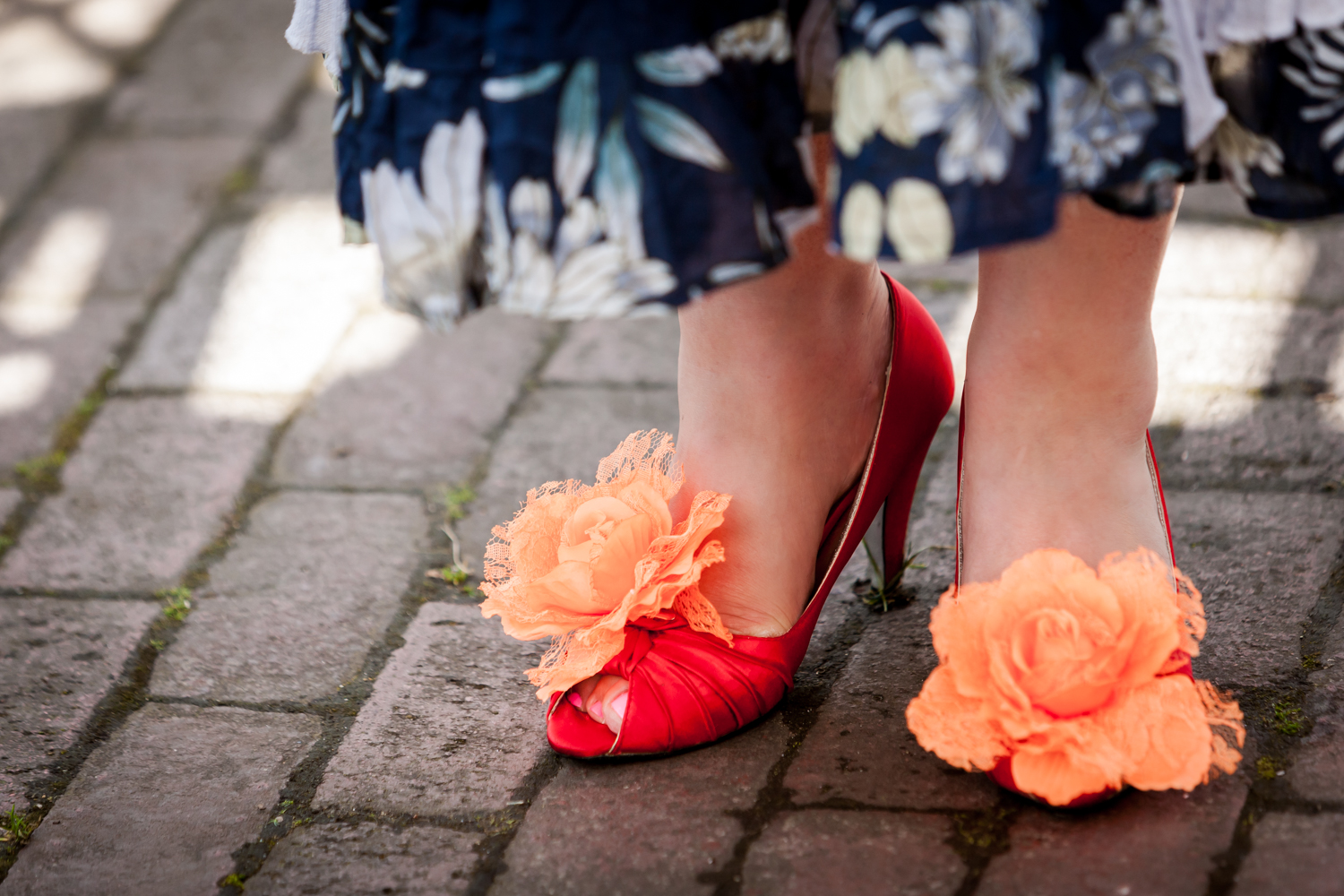 Close up on woman's feet wearing orange shoes with orange flowers