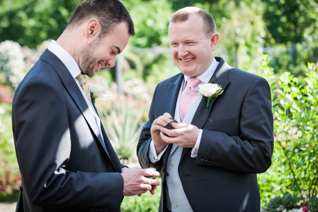 Two grooms holding rings at an Brooklyn Botanic Garden wedding