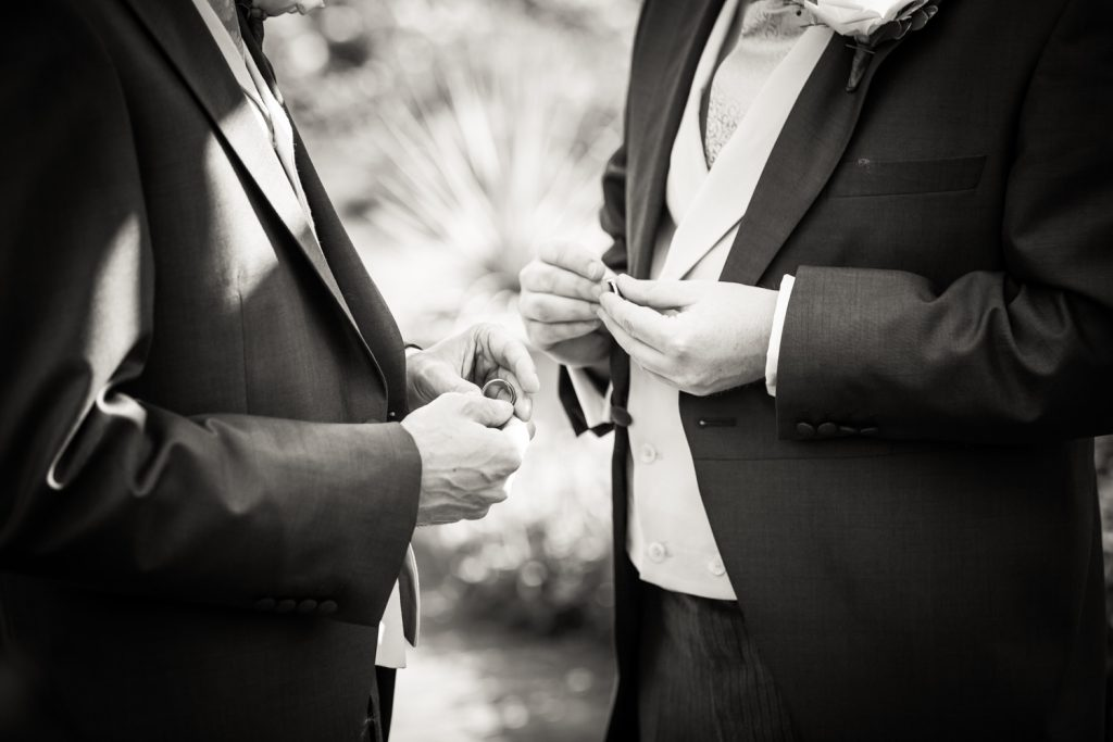 Black and white close up of two grooms holding wedding rings