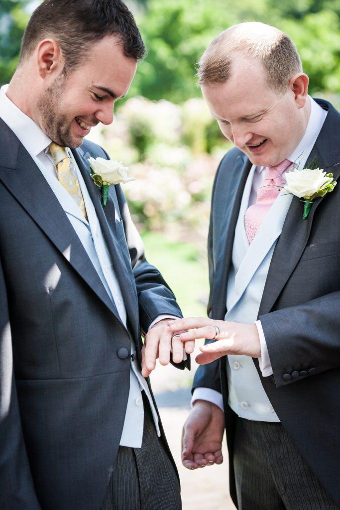 Two grooms looking at wedding rings at an Brooklyn Botanic Garden wedding