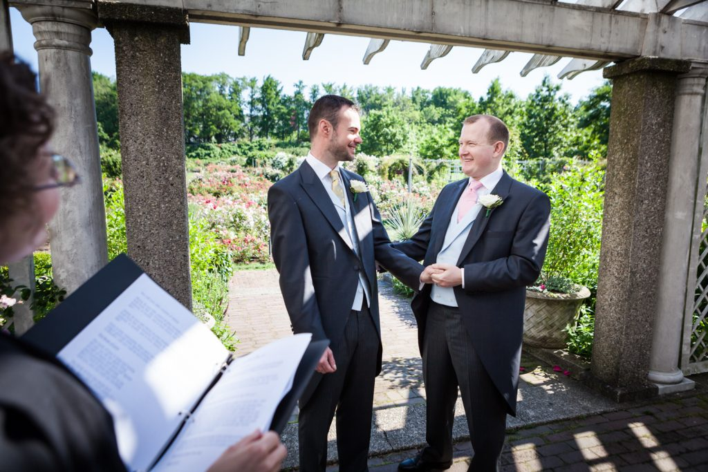 Two grooms during ceremony at an Brooklyn Botanic Garden wedding
