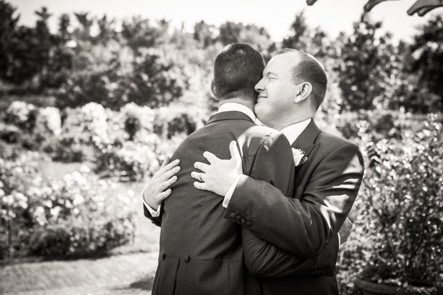 Black and white photo of two grooms hugging