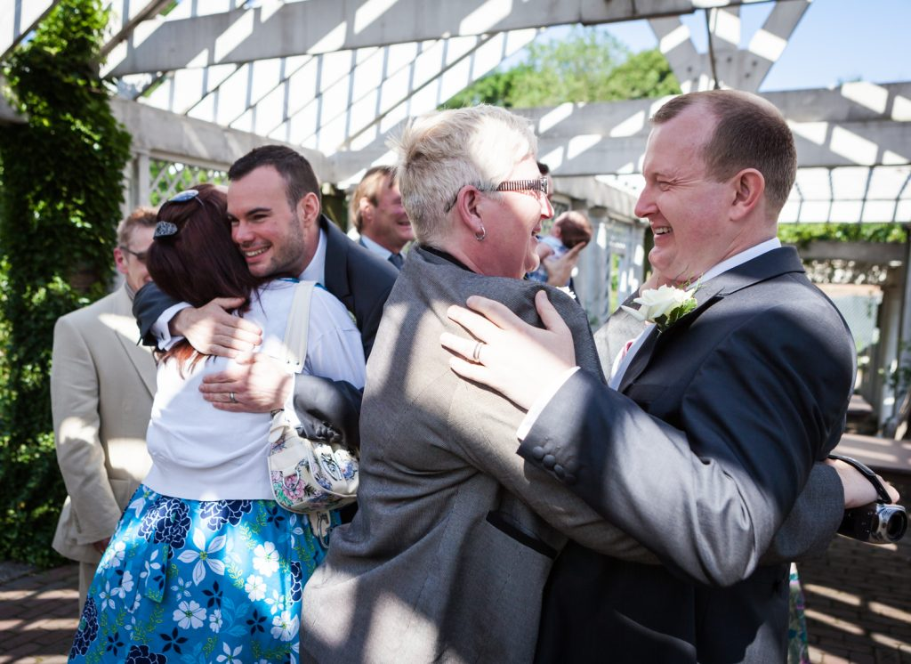 Two grooms hugging guests at an Brooklyn Botanic Garden wedding