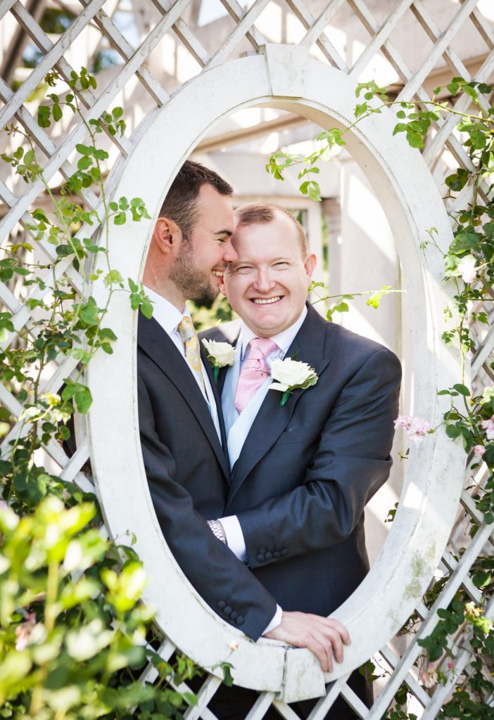 Two grooms looking out window of rose trellis at an Brooklyn Botanic Garden wedding