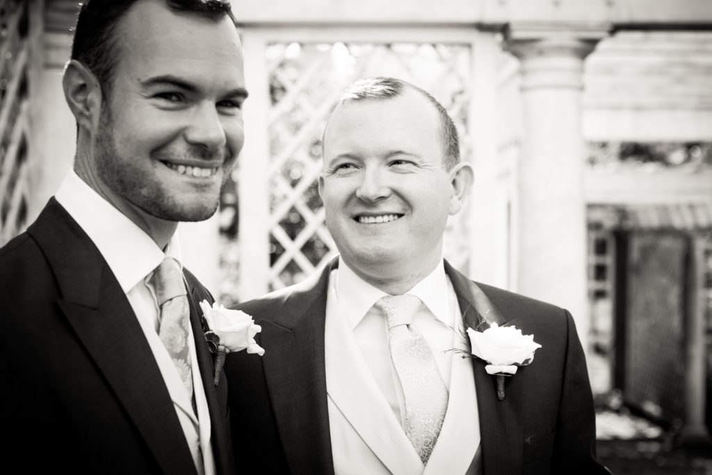 Black and white photo of two grooms in trellis