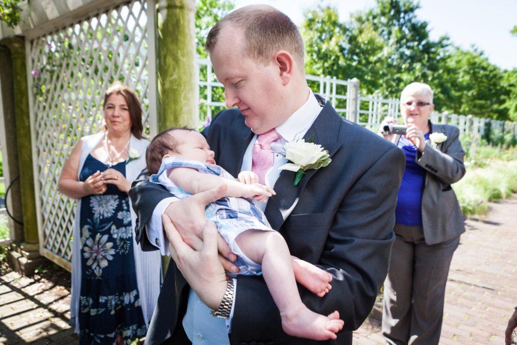 Groom holding baby at an Brooklyn Botanic Garden wedding