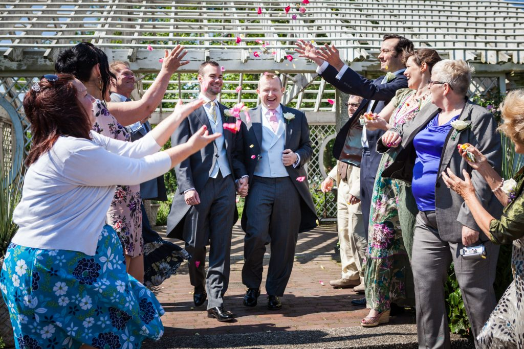 Guests throwing rose petals at two grooms at an Brooklyn Botanic Garden wedding