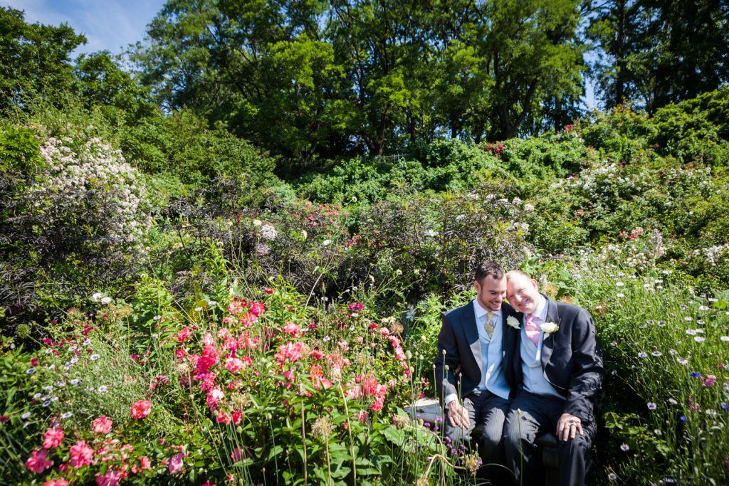 Two grooms sitting on bench in the middle of rose garden at an Brooklyn Botanic Garden wedding