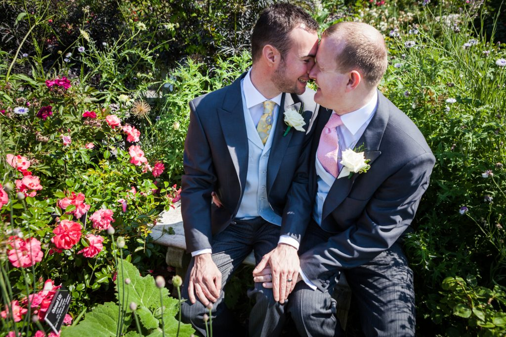 Two grooms touching foreheads in middle of rose garden at an Brooklyn Botanic Garden wedding