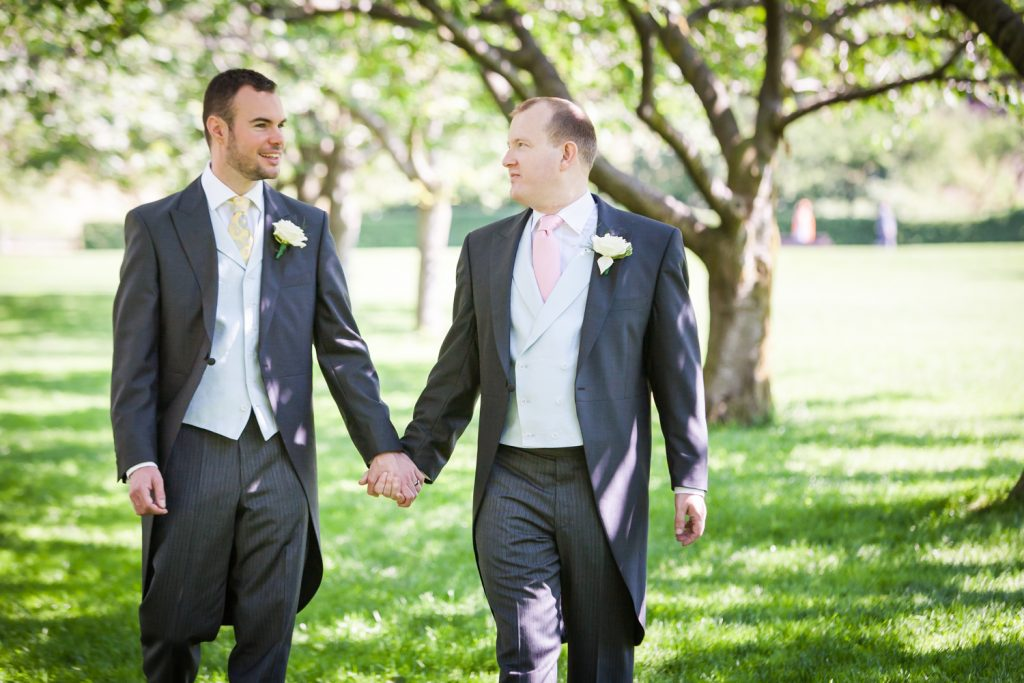 Two grooms holding hands and walking through Brooklyn Botanic Garden