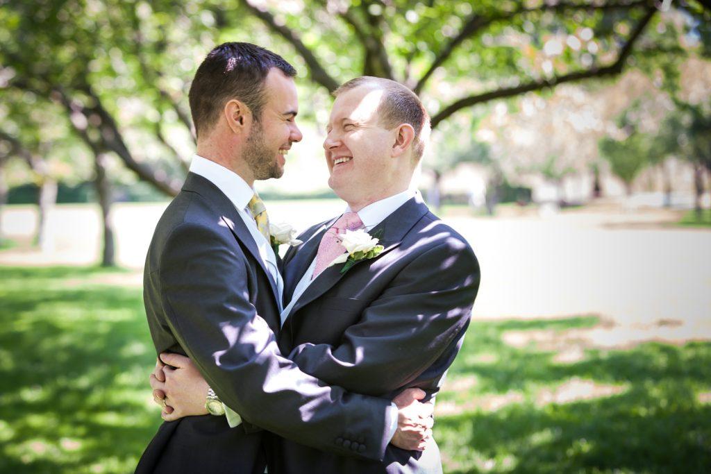 Two grooms hugging under trees in Brooklyn Botanic Garden