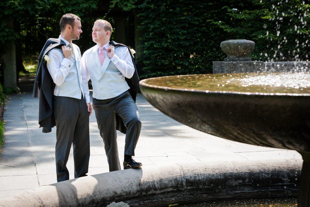 Two grooms holding jackets beside fountain in Brooklyn Botanic Garden